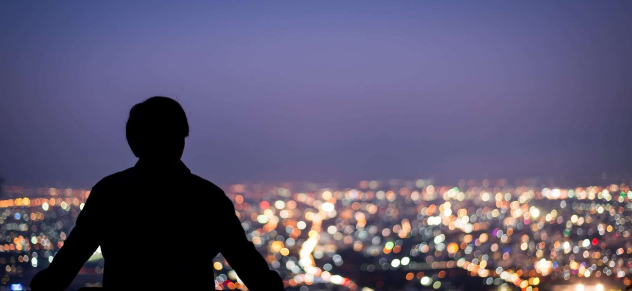 A silhouette of a man against city lights at night